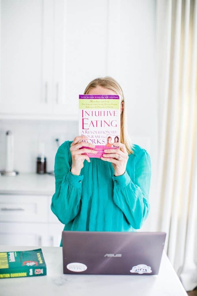 dietitian holding intuitive eating book